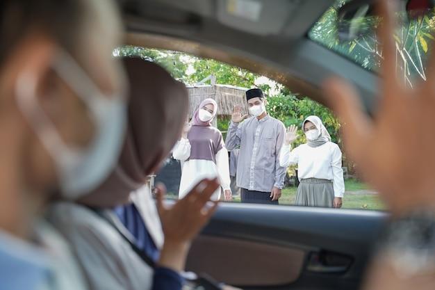 Muzułmańska rodzina w maskach macha do swoich braci i sióstr w samochodzie
