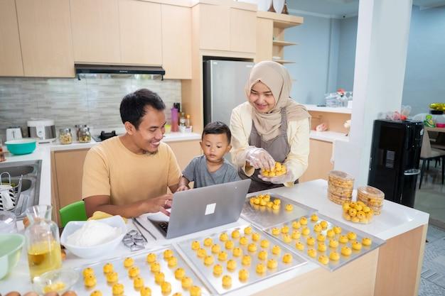 Muzułmańska rodzina wspólnie gotuje tartę z nastarami w domu. ojciec za pomocą laptopa