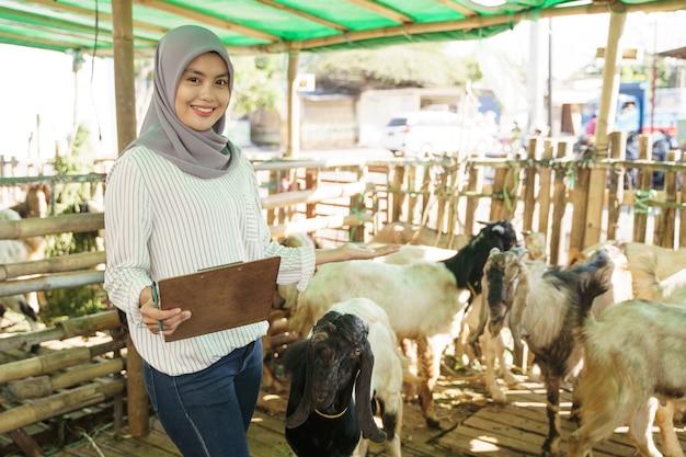 Muzułmańska rolniczka robi kontrolę dla swojej kozy w klatce