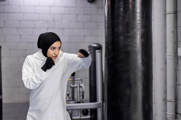 Muzułmańska sportsmenka uprawiająca kickboxing, uderzająca w ogromny worek treningowy, ubrana w hidżab. młoda silna arabska kobieta bokser ciężko trenuje.