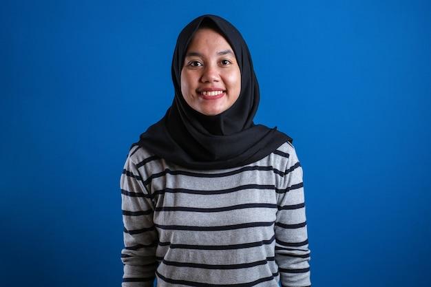 Muzułmańska studentka dziewczyna uśmiecha się do kamery na niebieskim tle z pewnym gestem.