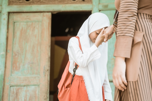 Muzułmańska uczennica potrząsa i całuje matkę przed pójściem rano do szkoły