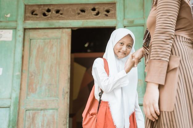Muzułmańska uczennica ściska matce rękę przed pójściem rano do szkoły