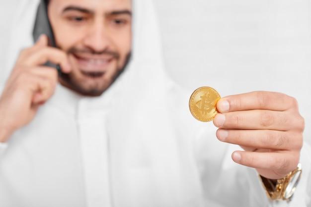 Muzułmański biznesmen wygląda na złotym bitcoinie