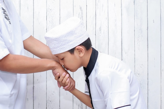 Muzułmański chłopiec witający się i proszący o przebaczenie, całując rękę podczas ramadanu i eid mubarak