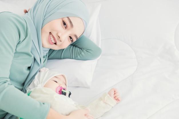 Muzułmański hidżab zostaje z dzieckiem na białym łóżku uśmiechając się do domu, matka opiekuje się niemowlęciem.