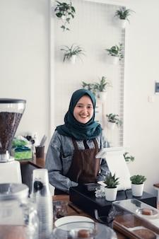 Muzułmański kelner w blacie kawiarni