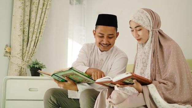 Muzułmański mąż pomagający żonie czytać koran