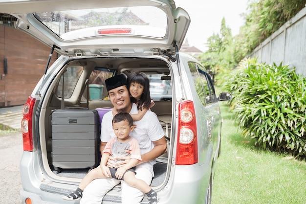 Muzułmański ojciec i jego dzieci siedzą na bagażniku samochodu eid mubarak holiday