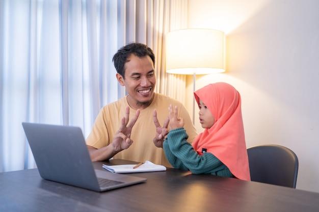 Muzułmański ojciec uczy córkę podczas wieczornych zajęć w domu