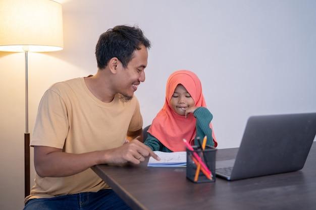 Muzułmański ojciec uczy córkę wieczorem podczas nauki w domu home