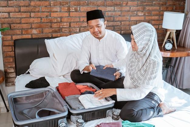 Muzułmański pary narządzanie odziewa na walizce