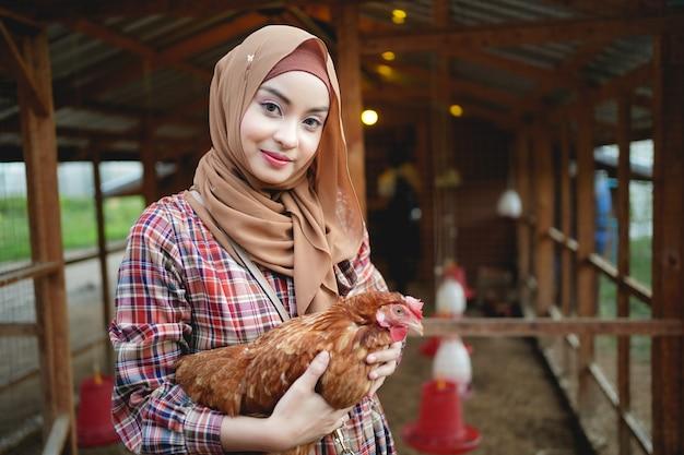 Muzułmański rolnik trzyma kurczaka w farmie kurczaków
