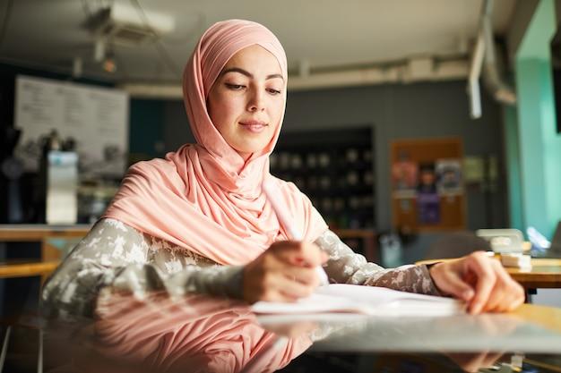 Muzułmański student uniwersytetu pisze w podręczniku
