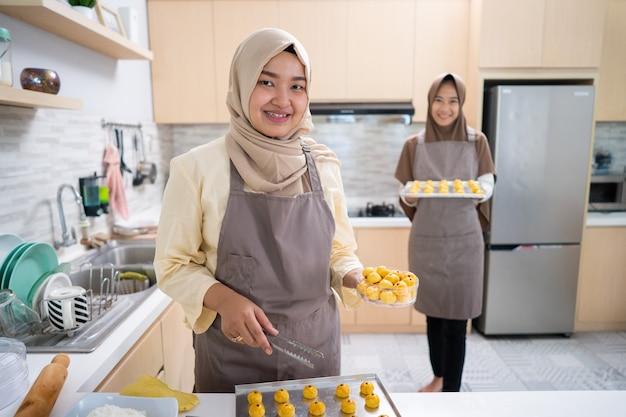 Muzułmański właściciel małej firmy robi domowej roboty przekąskę nastar na sprzedaż. piękna azjatycka kobieta z partnerem, gotowanie i trzymanie komputera typu tablet