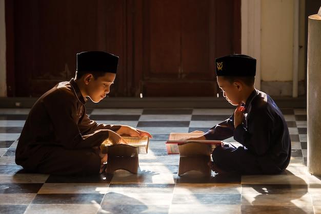 Muzułmańskie dziecko modli się, aby studiować z siostrą i bratem w meczecie w songkhla w tajlandii.