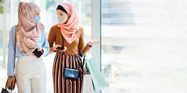Muzułmańskie dziewczyny w masce robią zakupy w centrum handlowym w nowym normalnym