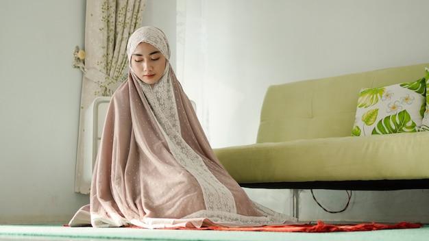 Muzułmańskie kobiety modlą się gestami powitania, nosząc mukenah