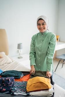 Muzułmańskie kobiety noszące hidżaby przygotowują ubrania do włożenia do walizki