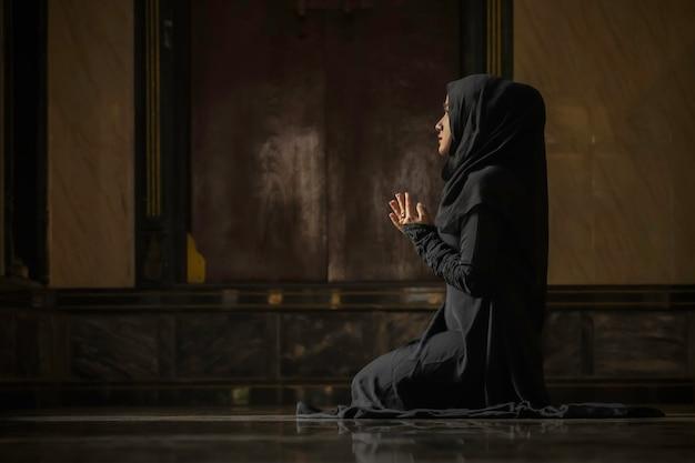 Muzułmańskie kobiety w czarnych koszulach wykonują modlitwę zgodnie z zasadami islamu.