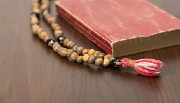 Muzułmańskie koraliki modlitewne i koran na białym tle na drewnianym tle. koncepcje islamskie i muzułmańskie
