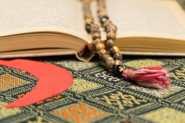 Muzułmańskie koraliki modlitewne i koran na macie modlitewnej. koncepcje islamskie i muzułmańskie