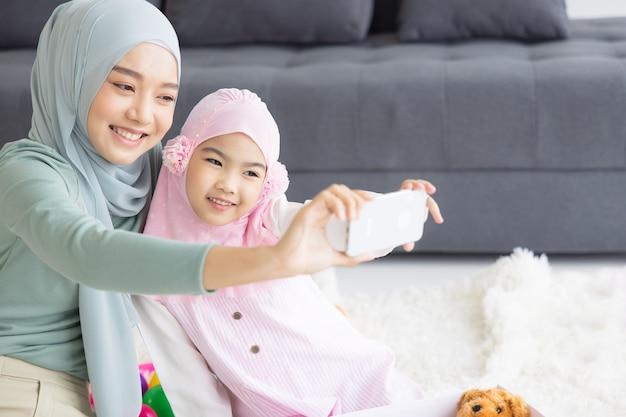 Muzułmańskie macierzyństwo przyszłe matki w hidżabie i robienie autoportretu w salonie