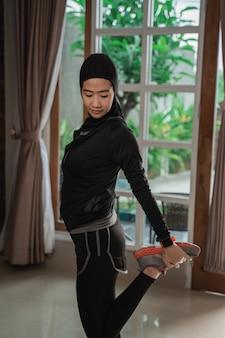 Muzułmańskie młode kobiety noszące odzież sportową hidżab robi rozciąganie