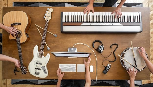 Muzycy pracują nad tworzeniem muzyki. na drewnianym stole znajdują się klawisze muzyczne, gitara akustyczna, gitara basowa, mikser, słuchawki, komputer.