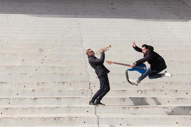 Muzycy wykonujący i skaczący
