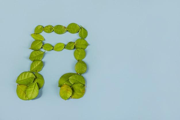 Muzyczne podwójne osiem notatek wykonane z zielonych liści na niebieskim tle