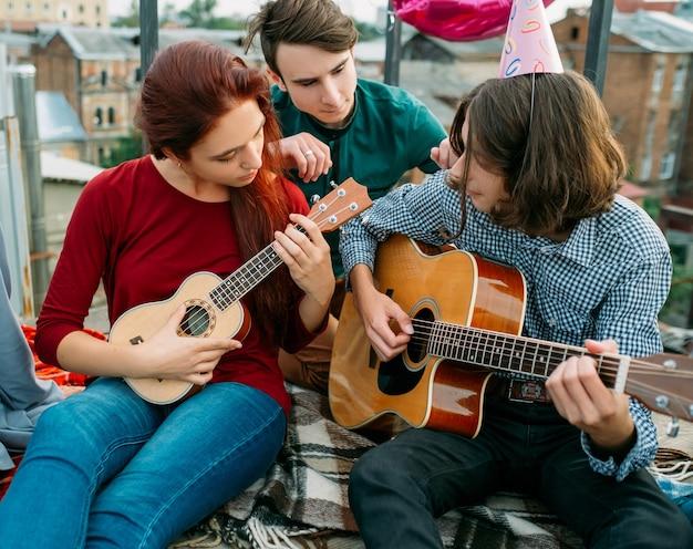 Muzyczny duet artystyczny. grają instrumenty strunowe na gitarze i ukulele. styl życia muzyka. wypoczynek nastolatków