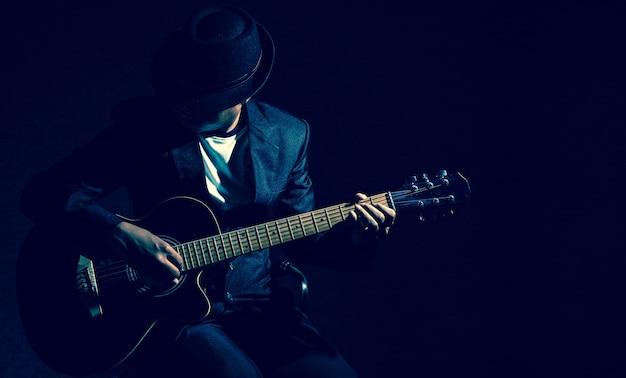 Muzyk bawić się gitarę na czarnym tle, muzyczny pojęcie