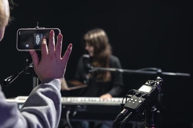 Muzyk dziewczyna nagrywa wideo na smartfonie stojąc na statywie, używając profesjonalnego mikrofonu, blogera lub nauczyciela muzyki w studio strzeleckim, siedząc przy pianinie.