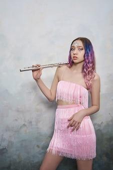 Muzyk dziewczyna z fletem w dłoniach w sukni scenicznej