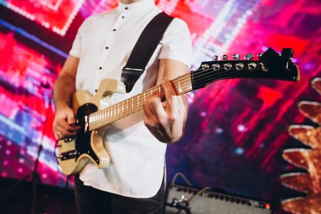 Muzyk gra na gitarze. aktor występuje na imprezie. instrument muzyczny.
