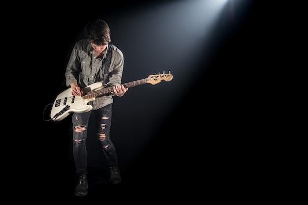 Muzyk gra na gitarze basowej, na czarnym tle z promieniem światła, emocjonalna gra, koncept muzyczny