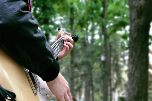 Muzyk gra na gitarze w parku