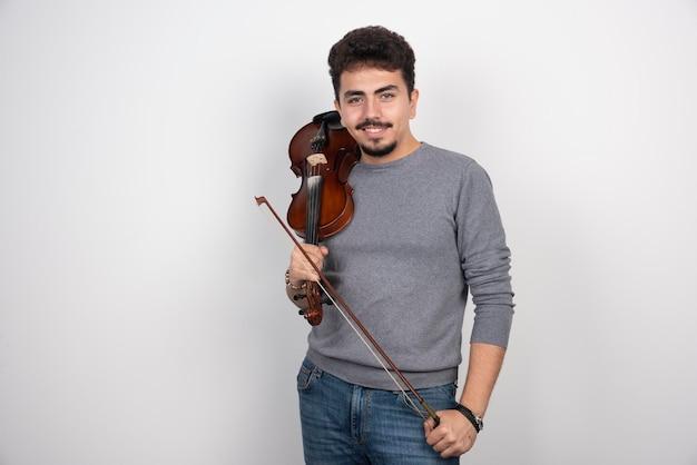 Muzyk gra na skrzypcach i wygląda na zainspirowanego i pozytywnego.