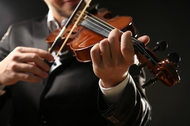 Muzyk gra na skrzypcach na czarno, z bliska