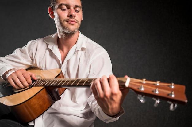 Muzyk grający na gitarze akustycznej