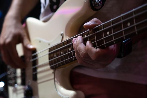 Muzyk grający na gitarze basowej biały z bliska.