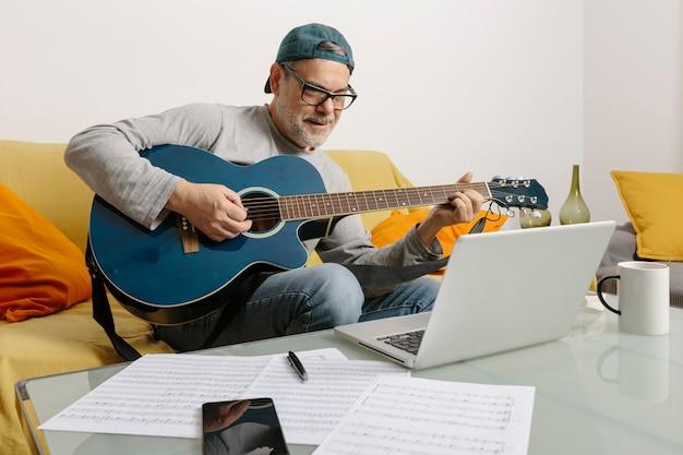 Muzyk grający na gitarze i komponujący muzykę z kolegami podczas wideokonferencji za pośrednictwem swojego laptopa