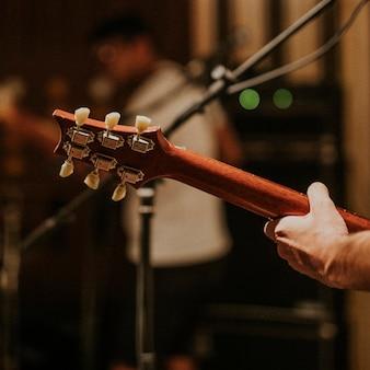 Muzyk grający na gitarze tło, fotografia estetyczna