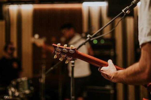 Muzyk grający na gitarze w tle, fotografia estetyczna