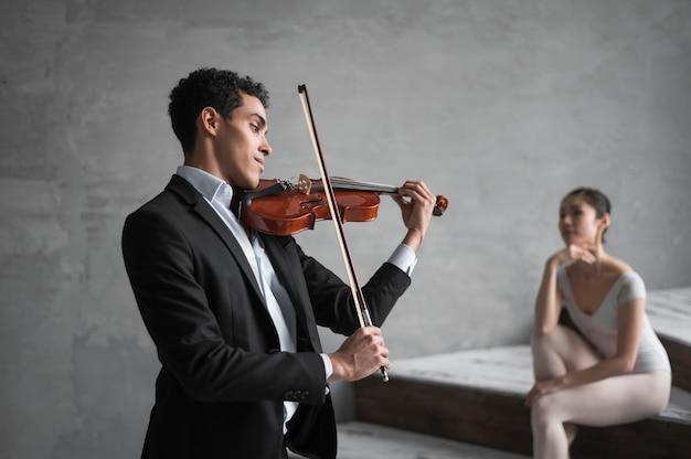 Muzyk grający na skrzypcach dla baleriny