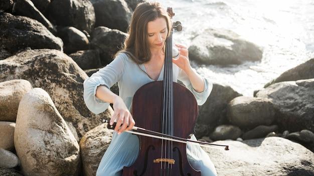 Muzyk grający na wiolonczeli nad oceanem