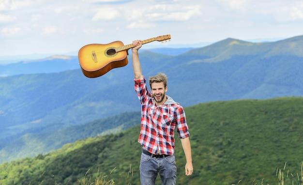 Muzyk hipsterski. pieśń piesza. mężczyzna muzyk z gitarą na szczycie góry. zainspirowany muzyk. inspirujące środowisko. letni festiwal muzyczny na świeżym powietrzu. cisza gór i dźwięk strun gitary.