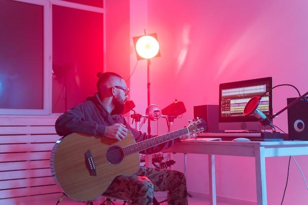 Muzyk i tworzenie muzyki - mężczyzna producent dźwięku pracujący w studiu nagrań.