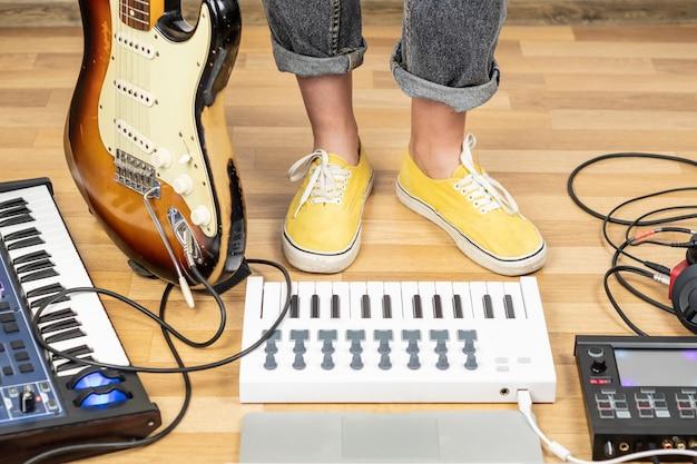 Muzyk indie z gitarą i syntezatorami w sali prób. młoda kobieta gitarzysta w żółtych butach w domowym studio, zbliżenie nogi w żółtych butach.